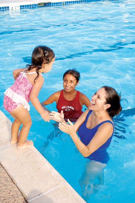 Child being encourage to jump into the pool by an instructor